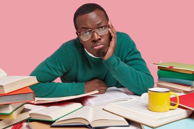 Boos donkere man heeft een verveelde uitdrukking, houdt de handen op de wang, draagt een bril en een groene trui, omringd met veel boeken