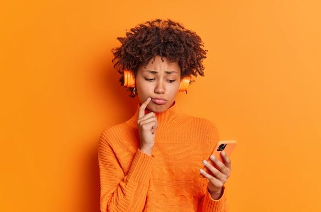 Boos duizendjarig meisje heeft gefrustreerde gezichtsuitdrukking leest tekstbericht luistert naar muziek uit afspeellijst gekleed in casual trui geïsoleerd over levendige oranje muur