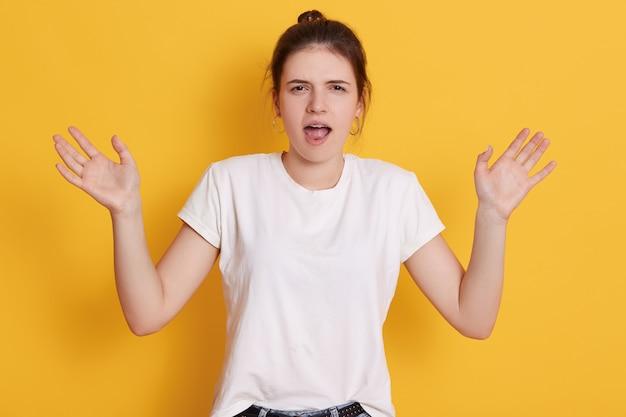 Boos emotionele jonge vrouw met donker haar en knoop, handen opzij spreiden en schreeuwen