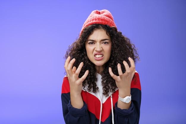 Boos en geïrriteerd stijlvol meisje balde handen in woede grimassen knijpende tanden van ergernis en...