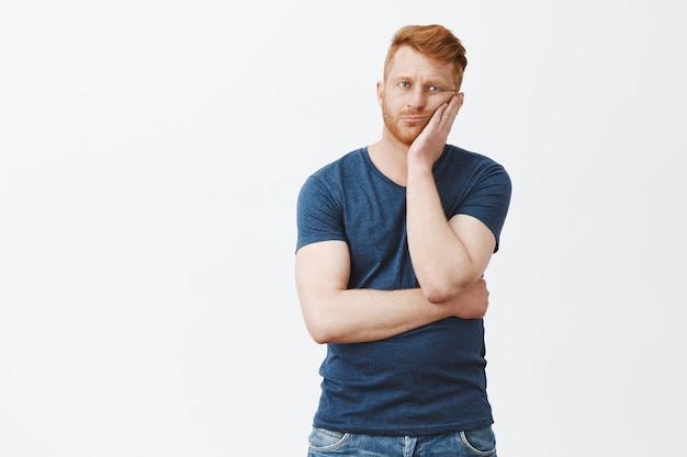 Boos en moe knappe mannelijke man met rood haar en borstelharen, leunend op de handpalm van verveling en onverschilligheid