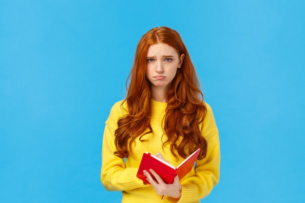 Boos en ongemakkelijk, droevig schattig roodharig meisje in gele trui, mokkend fronsend en camera depressief kijkend, rood notitieboekje vasthouden, iemands dagboek lezen, gedachten delen op papier, bedroefd