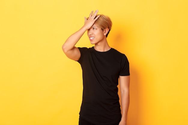 Boos en onrustige aziatische man breekt vergeetachtig voorhoofd, staande over gele muur