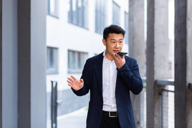 Boos en serieus succesvolle aziatische zakenman legt informatie uit aan werknemers die de telefoon gebruiken, spreekt buiten in de buurt van kantoor