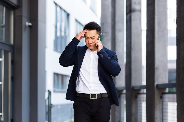 Boos en serieus succesvolle aziatische zakenman legt informatie uit aan werknemers die de telefoon gebruiken, spreekt buiten in de buurt van kantoor Premium Foto