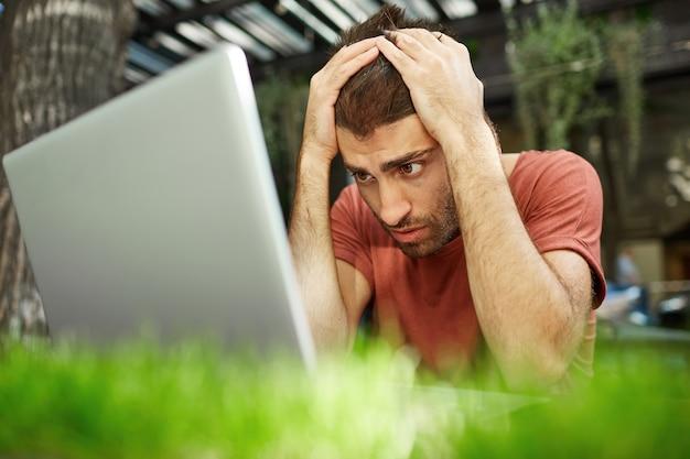 Boos en teleurgestelde knappe kerel die verdrietig naar laptopscherm kijkt terwijl hij buiten zit, bezig met afstandsbediening tijdens covid-19