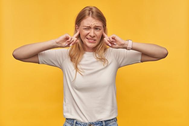 Boos geïrriteerde vrouw met sproeten in witte t-shirt kegelvormige oren door vingers en zichzelf te beschermen tegen lawaai op geel