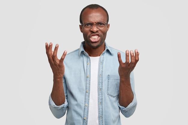 Boos geïrriteerde zwarte man schreeuwt en schudt zijn handpalmen, beu van ruzie, klemt zijn tanden op elkaar