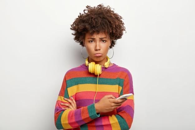 Boos gekrulde afro-vrouw met droevige blik, gebruikt mobiele telefoon, kan geen geld opnemen van online account, koptelefoon gebruiken om naar muziek te luisteren