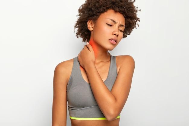 Boos gekrulde jonge vrouw lijdt aan nekpijn, gewond tijdens sporttraining, draagt casual grijze top