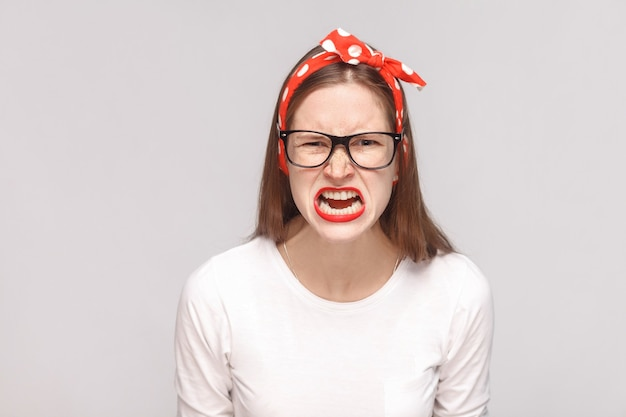 Boos gezicht schreeuwend portret van woede gekke bazige emotionele jonge vrouw in wit t-shirt met sproeten, zwarte bril, rode lippen en hoofdband. indoor studio opname, geïsoleerd op lichtgrijze achtergrond.