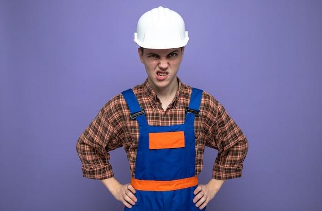 Boos handen leggen op hippe jonge mannelijke bouwer die uniform draagt