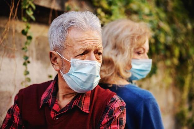 Boos hoger paar met beschermende maskers op rug aan rug zittend op de bank.