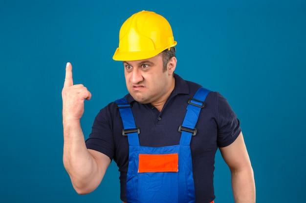 Boos in woedende man van middelbare leeftijd met uniforme constructie en veiligheidshelm wijzende vinger omhoog ontstemd en gefrustreerd over geïsoleerde blauwe muur