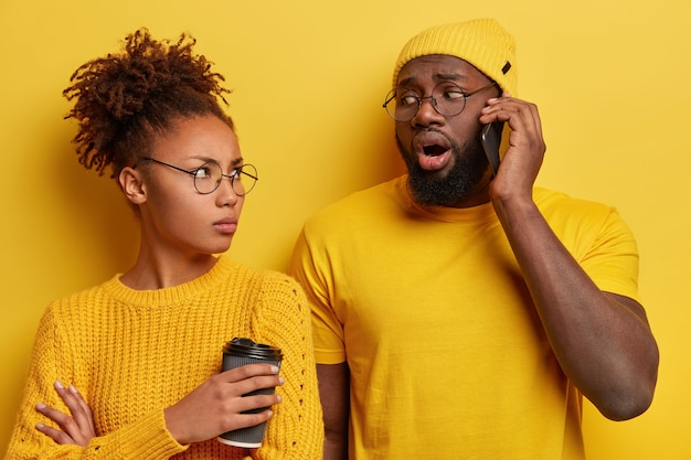 Boos jaloerse afro-vrouw kijkt naar man die op mobiele telefoon praat