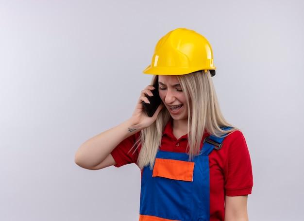 Boos jong blond meisje van de ingenieursbouwer in uniform en tandsteunen die op telefoon op geïsoleerde witte ruimte met exemplaarruimte spreken