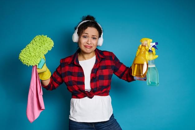 Boos jong gemengd ras vrouw met schoonmaakbenodigdheden en producten in de handen en kijken naar de camera met verdriet voor aanstaande huishoudelijk werk