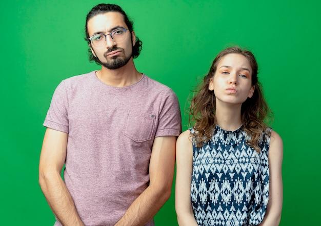 Boos jong koppel man en vrouw kijken camera met droevige uitdrukking op gezichten permanent over groene achtergrond