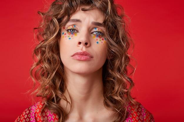 Boos jong krullend vrouwtje met feestelijke make-up, gekleed in een bonte top met een patroon, fronsen en kijken met gevouwen lippen, poseren