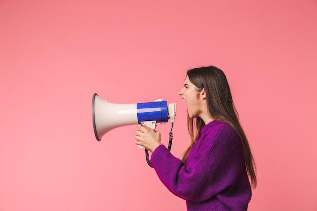 Boos jong meisje die sweater dragen die zich geïsoleerd over roze bevinden, die in een spreker schreeuwen