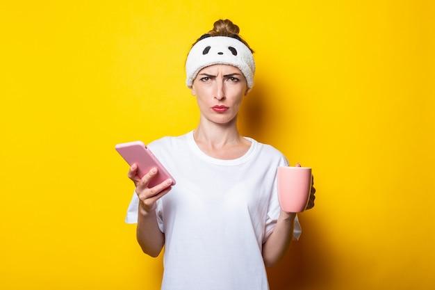 Boos jong meisje in een verband met een telefoon en een kopje koffie op een gele achtergrond