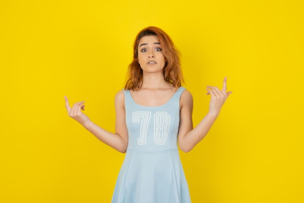 Boos jong meisje in jurk op gele muur
