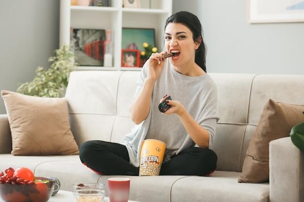 Boos jong meisje met tv-afstandsbediening eet koekje zittend op de bank achter de salontafel in de woonkamer