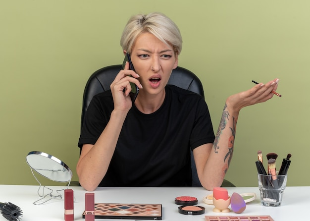 Boos jong mooi meisje zit aan tafel met make-uptools en spreekt op telefoon met make-upborstel geïsoleerd op olijfgroene muur