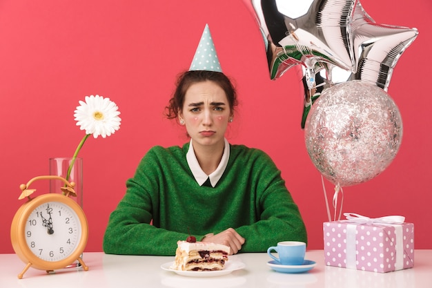 Boos jong nerd student meisje viert haar verjaardag zittend bij de tafel en op zoek