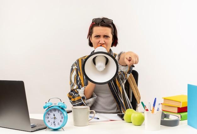 Boos jong studentenmeisje die glazen op hoofd dragen die aan bureau zitten dat door spreker spreekt en op wit wordt geïsoleerd wijzen