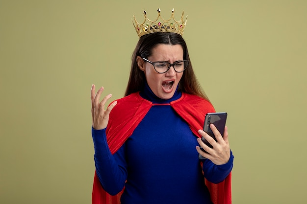 Boos jong superheld meisje bril en kroon houden en kijken naar telefoon geïsoleerd op olijfgroene achtergrond
