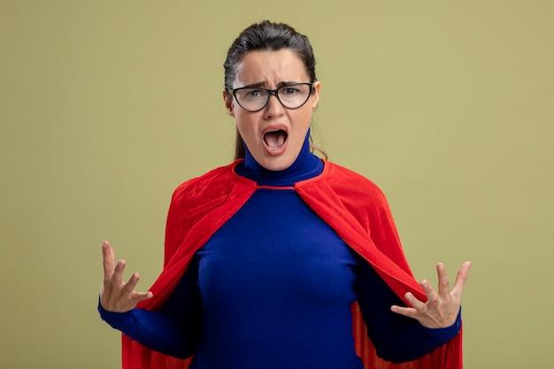 Boos jong superheromeisje die glazen dragen die handen spreiden die op olijfgroene achtergrond worden geïsoleerd