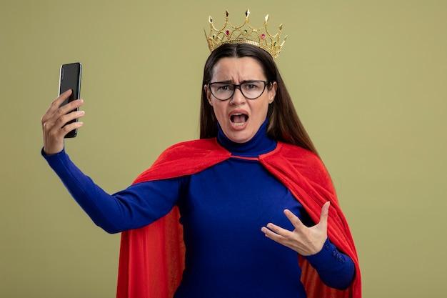 Boos jong superheromeisje die glazen en de telefoon van de kroonholding dragen die op olijfgroen wordt geïsoleerd