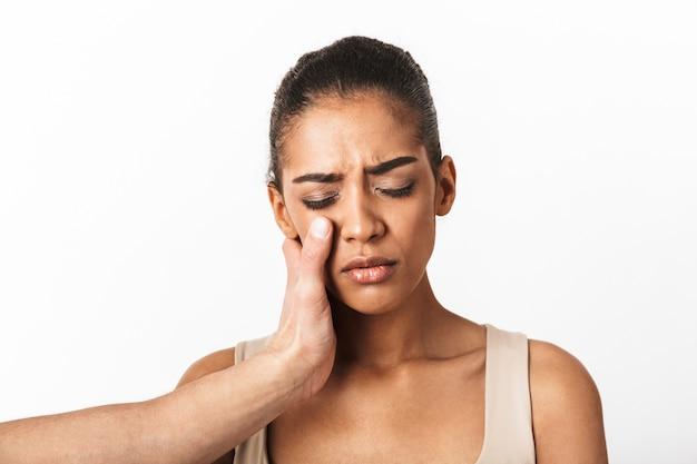 Boos jonge afrikaanse vrouw huilen met man's hand op haar gezicht geïsoleerd op wit
