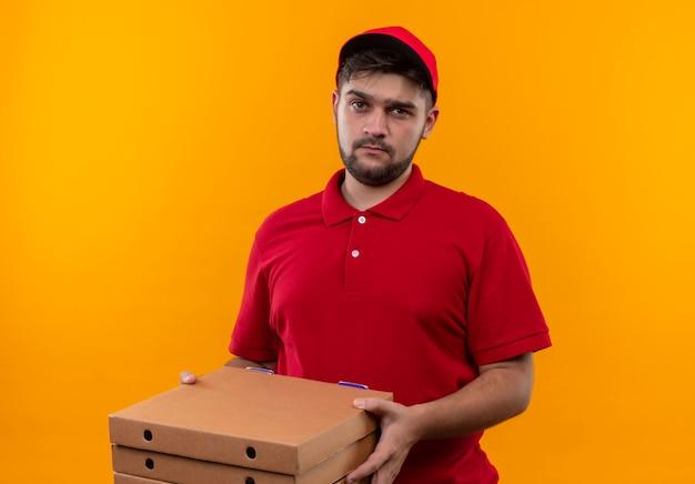 Boos jonge bezorger in rood uniform en pet bedrijf stapel pizzadozen camera kijken met droevige uitdrukking op gezicht