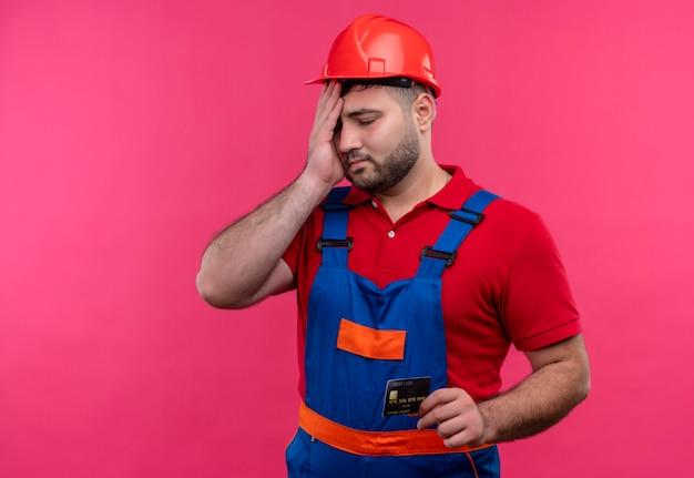 Boos jonge bouwersmens in eenvormige bouw en de creditcard van de veiligheidshelmholding kijkt verward