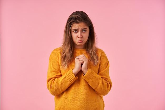 Boos jonge brunette vrouw met casual kapsel haar opgeheven handen vouwen en jammerlijk kijken met pruilende lippen, poseren op roze