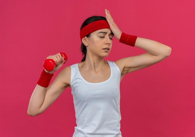 Boos jonge fitness vrouw in sportkleding met hoofdband halter in opgeheven hand houden op zoek verward met hand op haar hoofd staande over roze muur