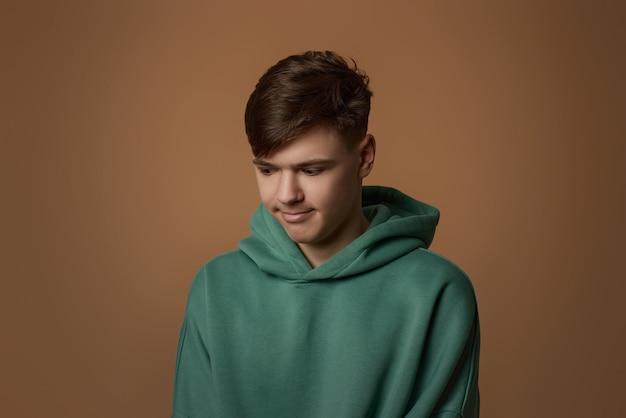 Boos jonge kerel in sweatshirt geïsoleerd op bruine achtergrond