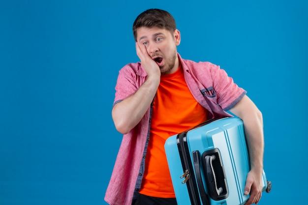 Boos jonge knappe reiziger man met koffer, op zoek verward