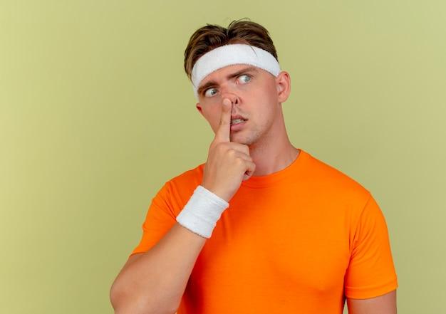 Boos jonge knappe sportieve man met hoofdband en polsbandjes kant kijken en vinger op neus zetten geïsoleerd op olijfgroene achtergrond