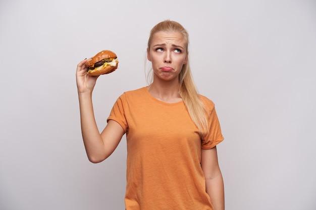 Boos jonge langharige blonde dame in oranje t-shirt droevig opzij kijken en rimpelend voorhoofd terwijl ongezond voedsel in opgeheven hand, staande tegen een witte achtergrond