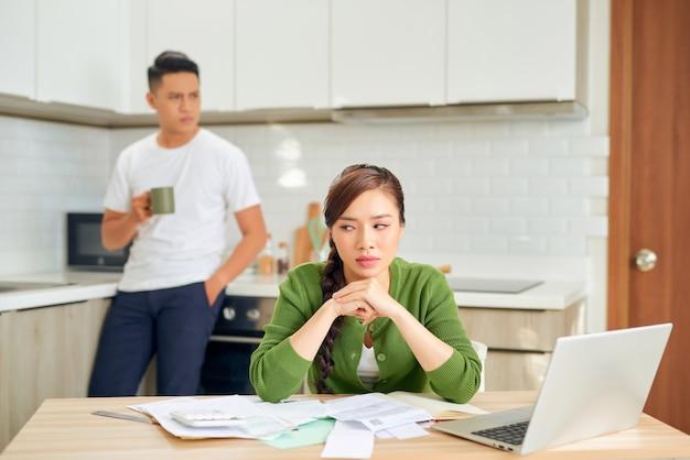 Boos jonge man met financiële rekeningen met een conflict met de vrouw thuis