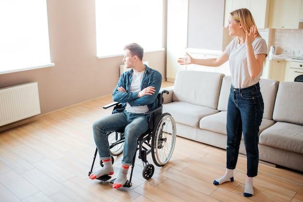 Boos jonge man op rolstoel blik op venster. kerel met speciale behoeften en handicap. de jonge vrouw bevindt zich naast en debatteert met hem. stress en emotionele ziekte.