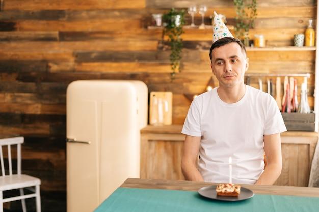 Boos jonge man zit op de verjaardagstaart en kijkt met droevige ogen erop. concept van eenzaamheid in quarantaine tijdens de coronavirus pandemie covid-19.