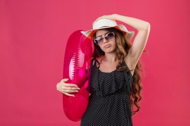 Boos jonge mooie reiziger meisje in jurk in polka dot in zomer hoed dragen zonnebril houden opblaasbare ring kijken camera met droevige uitdrukking op gezicht staande over roze achtergrond