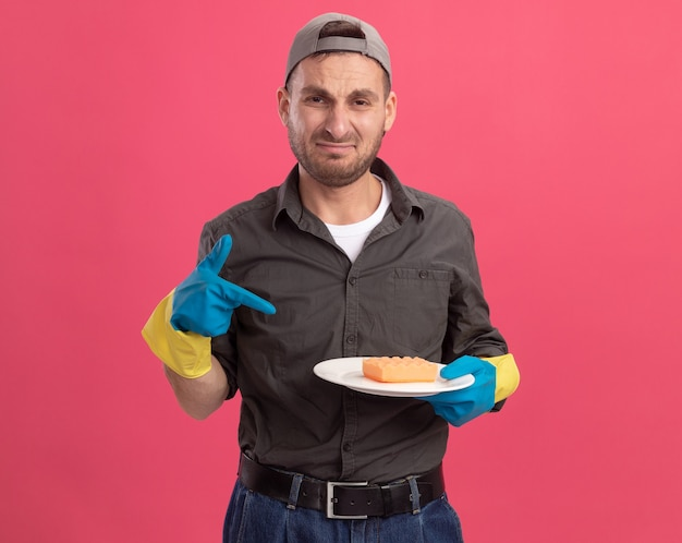 Boos jonge schoonmaakster met vrijetijdskleding en pet in rubberen handschoenen met plaat en spons wijzend met wijsvinger naar plaat huilen tuitende lippen staande over roze muur
