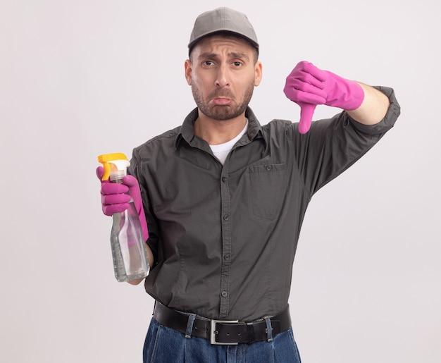 Boos jonge schoonmakende man die vrijetijdskleding en pet in rubberen handschoenen draagt die spuitfles houdt die met droevige uitdrukking kijkt die duimen naar beneden toont die zich over witte muur bevinden