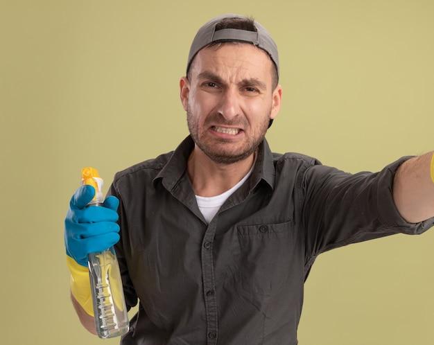 Boos jonge schoonmakende mens die vrijetijdskleding en glb in rubberhandschoenen draagt die nevelfles houdt die met droevige uitdrukking kijkt die zich over groene muur bevindt