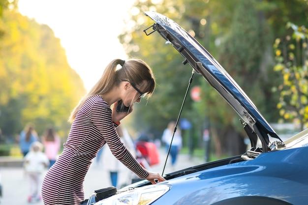 Boos jonge vrouw chauffeur boos praten op mobiele telefoon met hulpdienst in de buurt van een kapotte auto met open kap op een straat in de stad.